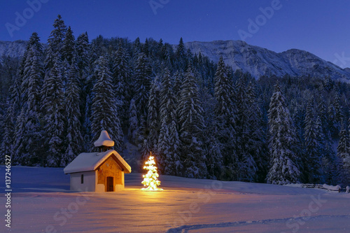 Illuminated Christmas tree in front of a chapel in winter, Bavaria, Upper Bavari Poster