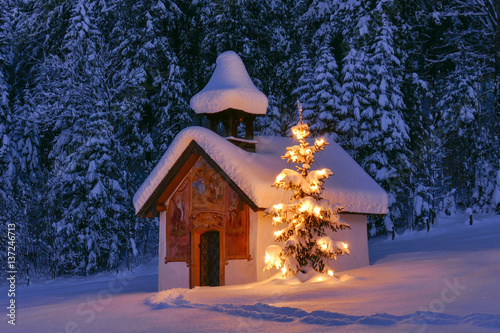 Illuminated Christmas tree in front of a chapel in winter, Bavaria, Upper Bavaria, Germany, Europe © pwmotion