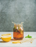 Summer cold Iced tea with fresh bergamot, mint and lemon in glass jar with splashes on light table, grey concrete wall at background, copy space. Food in motion concept