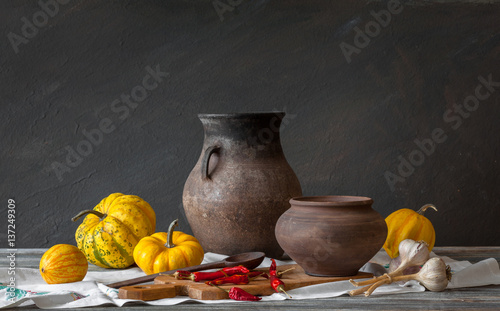 Still life in a rustic style. A set of clay dishes and pumpkin on a wooden table. Natural light from the windows. © symbol344