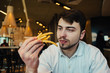 a young man sitting in a restaurant and holding hands french fries and going to eat