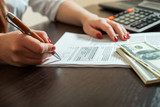 Woman bookkeeper signs accounting documents