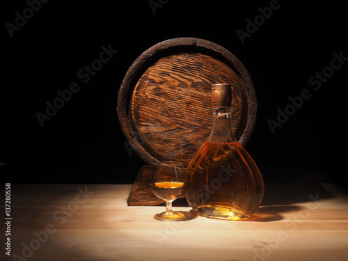 Glass of cognac with barrel on wooden backgroun Poster