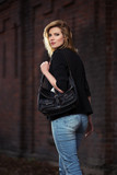Young fashion blond business woman with handbag walking on city street