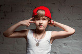 Portrait of cool young hip hop boy in red hat and red pants and white shirt in the loft - 137305525