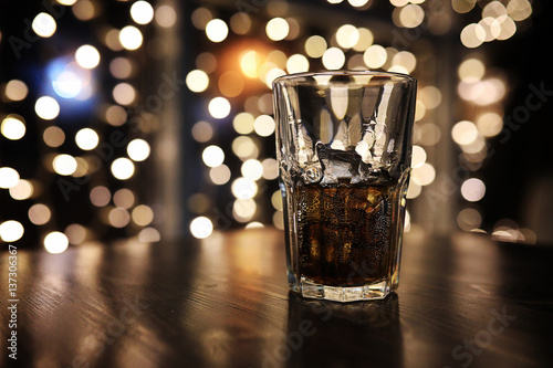 glass of alcohol with ice on blured background with circle bokeh Poster