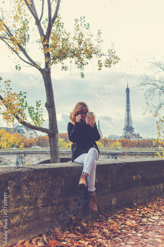 Poster Cute girl using cellphone with Eiffel tower in the background, Paris - France