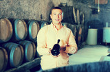 man with bottle of wine in winery cellar.