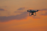flying drone quadrocopter at sunset