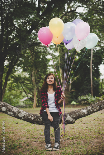 Poster Young hipster woman sitting on tree branch with colorful of balloons in hand, Relaxing enjoy holiday