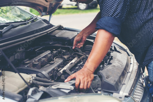 Man with checking car engine. Poster