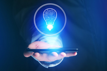 Businessman hand holding mobile phone with bulb idea icon