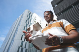 Low angle view of confident Indian man standing in front of modern skyscraper and holding drone remote controller in hands