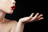 Beautiful young woman blowing a kiss from her hand. Model with perfect dark redl lips and manicured red nails