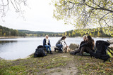 Friends Looking At Man Preparing Bonfire On Lakeside Camping