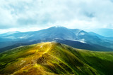 Summer mountain landscape. Mountain path. Landscape with mountains and green hills with blue sky and clouds.