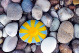 Sun painted on pebble with stones background - 137364359