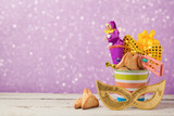 Purim holiday concept with carnival mask and gifts over bokeh lights background