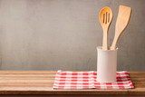 Wooden kitchen utensils on table with tablecloth over grunge wall background with copy space for product montage display
