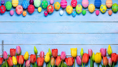Easter Eggs And Tulips In Frame On Blue Table