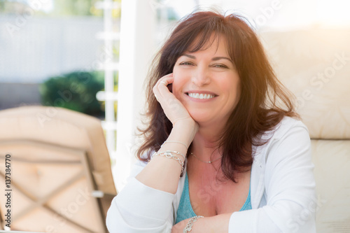 Attractive Middle Aged Woman Smiles On The Patio.