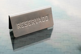 Metal reserved reservado sign on glass table in restaurant in Spain