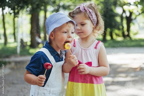 Happy children taste candy on a stick Poster
