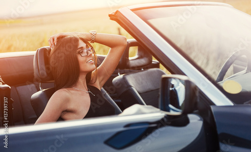 Foto op Canvas Snelle auto s beautiful young woman posing near a car on the road