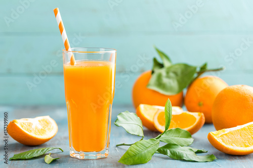 Foto op Canvas Sap Orange juice in glass and fresh fruits with leaves on wooden background, vitamin drink or cocktail