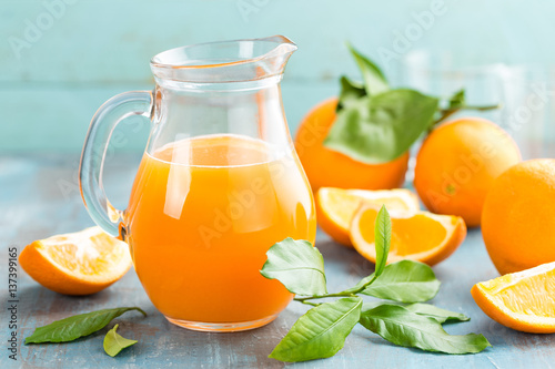 Deurstickers Sap Orange juice in glass and fresh fruits with leaves on wooden background, vitamin drink or cocktail