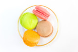 Sweet and colourful french macaroons or macaron in a glass bowl on white background, Top view with copy space for your text.