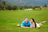 Young beautiful couple with coconuts holding hands, lying at green grass of golf course in summer. man wear the blue shirt and the girl in a white dress. Concept of honeymoon