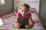 Young girl lying on the bed with headphones and tablet