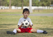 Asian boy with soccer on green field