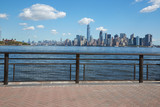 New York city skyline view and Ellis Island from empty dock terrace in summer, blue sky - 137483333