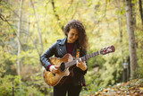 Beautiful young woman playing guitar on forest, fashion lifestyle. Girl wearing black jacket.