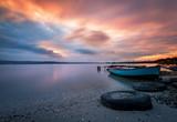 Beautiful majestic sunrise by the lakeside with fishing boats. Nature landscape.