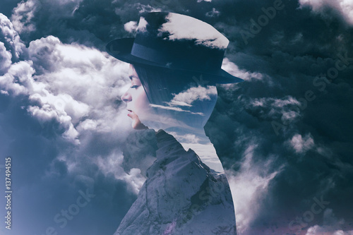 Multiple exposure of girl wearing hat, mountainscape and stormy cloudscape - 137494515