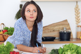 Young  woman is making online shopping by tablet computer and credit card. Housewife found new recipe for  cooking in a kitchen