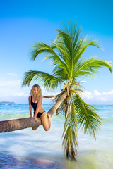 young sexy girl sitting on palm tree over blue sea