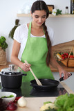 Young hispanic woman is cooking in the kitchen. Housewife fry the meat in a frying pan
