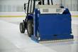 Resurfacing machine cleaning ice of hockey rink.