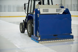 Resurfacing machine cleaning ice of hockey rink.