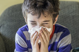 Young boy sneezing into a tissue while at home sick in pyjamas