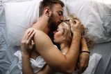 Young adult heterosexual couple lying on the bed in the bedroom
