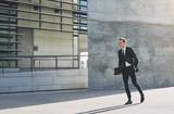 Male in dark suit rushing down street