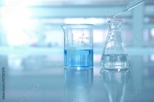 beaker and flask with blue solution and drop of water in science