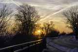 Silhouette of person walking on path during early morning sunrise at dawn, winter