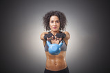 Young attractive female doing kettle bell exercise on grey background