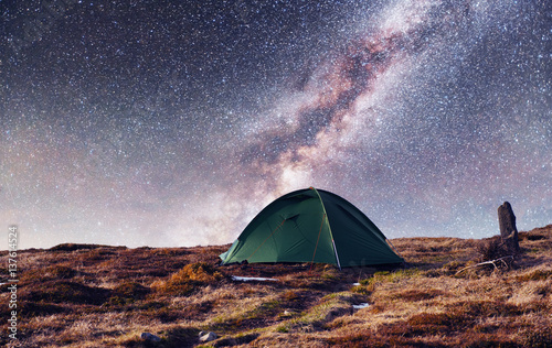 the starry sky above the tent in the mountains. Magic event in f